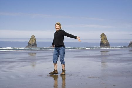 A woman on the beach with arms out stretched enjoying the sun