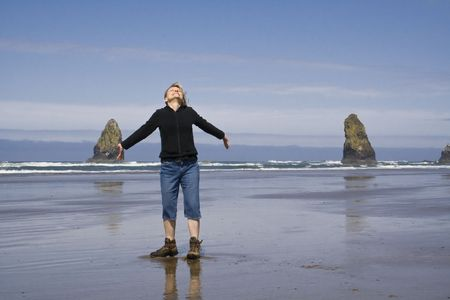 A woman on the beach with arms out stretched enjoying the sun photo