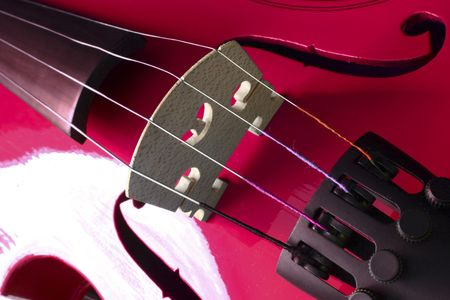 A close up of a red violin on a black background