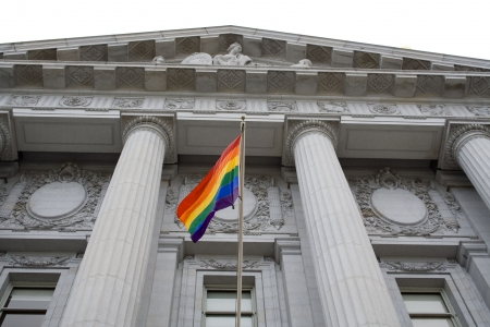 Lesbian, gay, bisexual, and transgender pride flag flying outside a government building photo