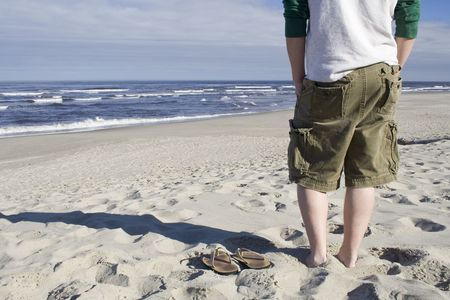 A young man stands next to his empty sandals on the beach