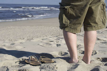 A young man stands next to his empty sandals on the beach photo
