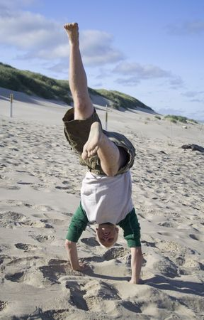 A young man doing a handstand on the beach photo