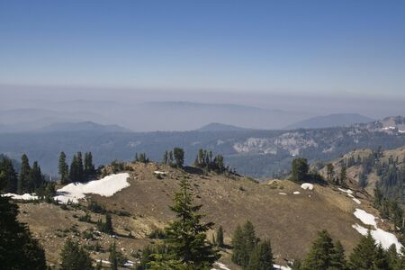 Smoke and smog from the California wildfires hangs in the sky over the mountains