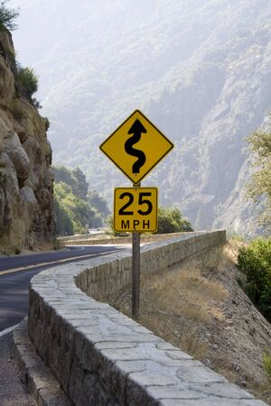 cautionary: A winding mountain road and cautionary sign