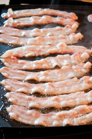 streaky: Fresh bacon frying on a griddle for breakfast