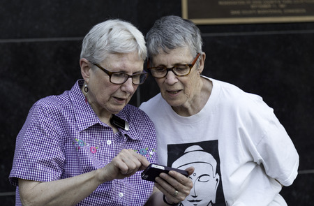 An older lesbian couple sharing the news via their phone after a judge struck down Wisconsin