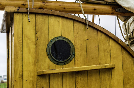 A port hole on an old wooden ship photo