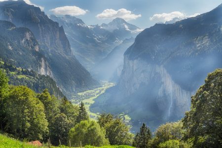 shadowed: The sun casts hazy rays of light over the deeply shadowed Lauterbrunnen valley in the canton of Bern