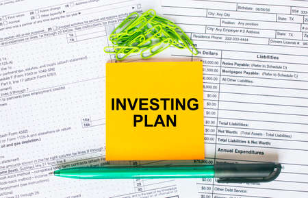 Text Investing Plan on note paper with pen, compass and paper clips. Business and financial conzept 版權商用圖片