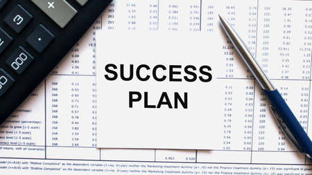 Work smarter text Success Plan on white sheet with pen, calculator and tables