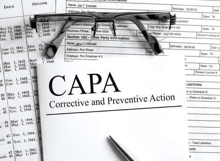 Paper with text CAPA Corrective And Preventive Action on a table