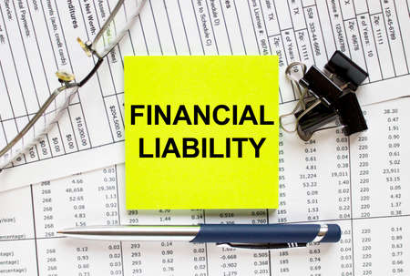 Text Financial Liability on financial tables with pen, glasses and paper clips. Business and financial conzept