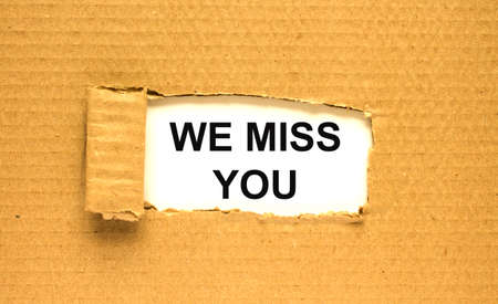 The text We Miss You appearing behind torn brown paper