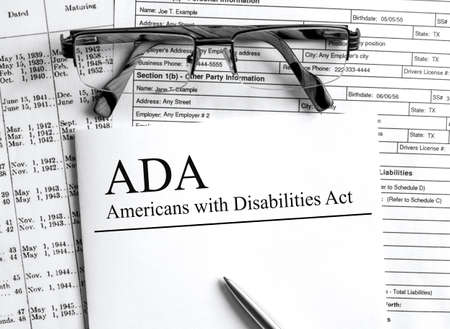 Paper with text ADA Americans with Disabilities Act on a table Banco de Imagens