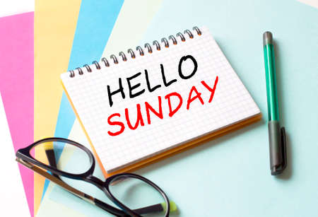 The Notepad with the text Hello Sunday is on colored paper with glasses and a pen. Concept photo Stock fotó