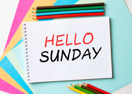 The Notepad with the text Hello Sunday is on colored paper with color pencils. Concept photo
