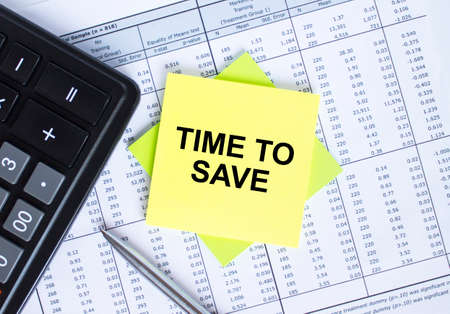 Sticker with text Time To Save lying on the financial tables. Calculator with metal pen. Business and financial concept