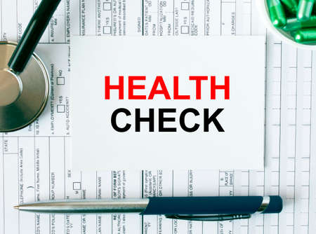 Text Health Check on the white card with the stethoscope, pen, green pills and medical documents. Medical concept photo