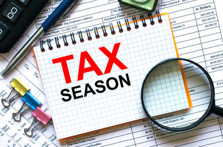 Text Tax Season on notepad with calculator, clips, pen on financial report. Financial and business concept photo