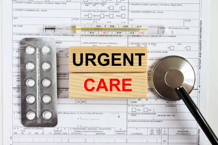 Text Urgent Care on wooden cubes with a stethoscope and pills are on medical documents.