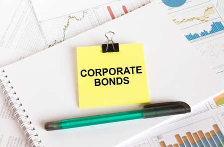 A yellow sticker with text Corporate Bonds is in a Notepad with a green pen financial charts and documents. Business and financial concept