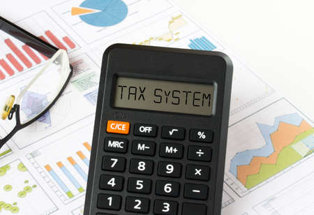 Calculator with text on the display Tax System it is on the financial charts with eyeglasses, can be use as financial and business concept