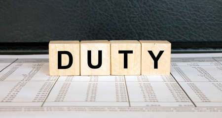 Word Duty made with wood toy blocks on financial tables. Business concept