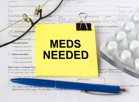 A yellow sticker with the text Meds Needed is on the health insurance form with pills and eyeglasses. Medical concept