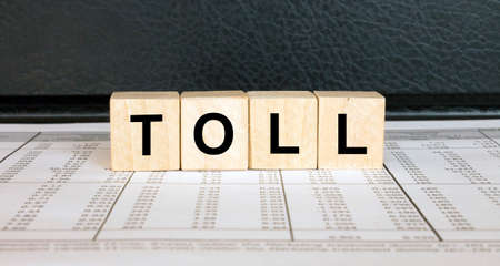 Word Toll made with wood toy blocks on financial tables. Business concept 版權商用圖片