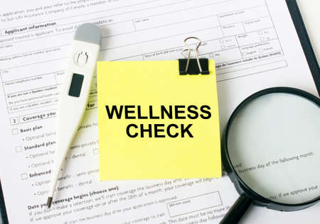 The text Wellness Check is written on a yellow sticker next to the magnifying glass and electronic thermometer. Medical concept