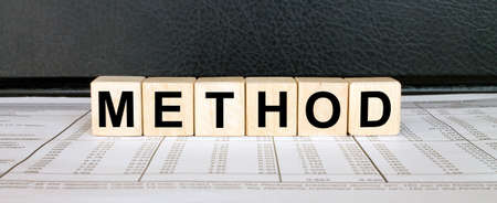 Word Method made with wood toy blocks on financial tables. Business concept