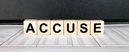 Word Accuse made with wood toy blocks on financial tables. Business concept