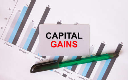 Business card with text Capital Gains. Diagram and green pen. Concept photo