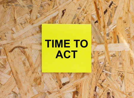 Yellow Sticker with text Time To Act on the wooden background. Concept photo Foto de archivo