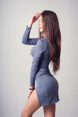 Beautiful young brunette girl with long hair in thin dress