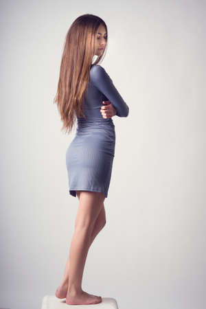Young slim girl turned in tight dress