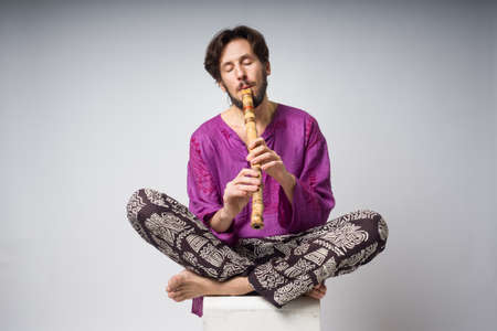 The musician who plays ethnic instruments.  The man sitting in the lotus position plays the flute. The young man in the national Indian clothes
