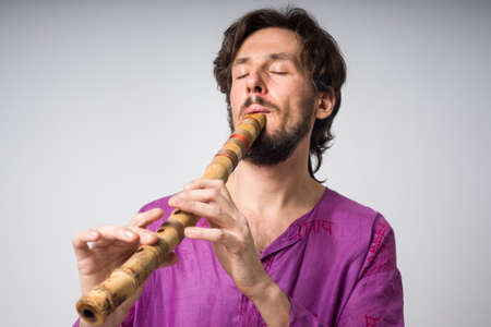 The musician who plays ethnic instruments. Man playing the Japanese flute. A young man in traditional Indian clothing