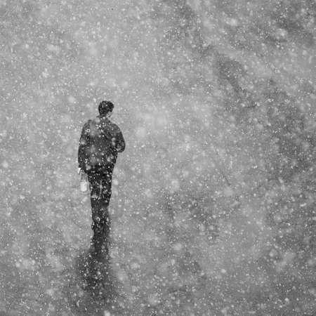 Grote sneeuwvlokken vallen op de lopende man. Artistieke fotografie met sneeuw