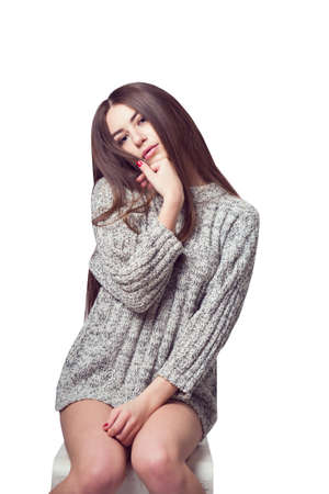 Young beautiful girl sitting on a chair. On a white background. In one gray sweater. Photosession of a sexy brunette. Different emotions. Pending. Hand on the chin. Playful pose. On a white background