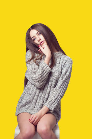 Young beautiful girl sitting on a chair. On a white background. In one gray sweater. Photosession of a sexy brunette. Different emotions. Pending. Hand on the chin. Playful pose. On a yellow background Imagens
