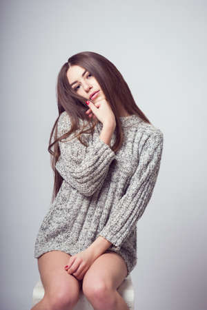 Young beautiful girl sitting on a chair. On a white background. In one gray sweater. Photosession of a sexy brunette. Different emotions. Pending. Hand on the chin. Playful pose.