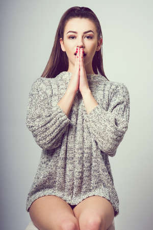 Young beautiful girl sitting on a chair. On a white background. In one gray sweater. Photosession of a sexy brunette. Different emotions. Folded arms at the mouth. A sign of surprise.