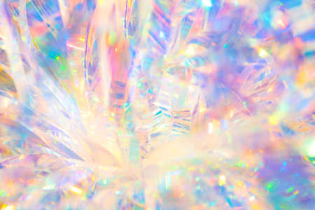 Abstract radiant festive merry holiday backdrop texture image of holographic iridescent metallic foil ribbon decoration with warm bright glow and sparkling crystal ice reflections and bokeh light