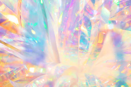 Festive cheerful abstract image texture of holographic foil ribbon in candy colors with sparkling light reflections