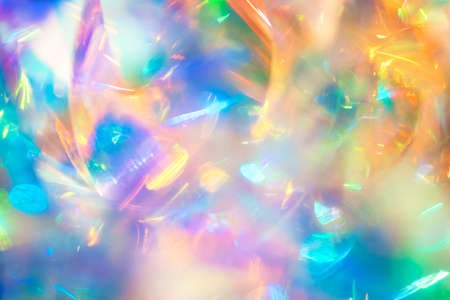 Abstract night club party poster background image of multicolored holographic foil with blue green and gold shiny bokeh light effect and dynamic motion blur