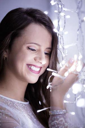 Portret van een gelukkige aantrekkelijke vrouw in elegante witte fonkelende kleding met een gloeiend gezicht die bij koordlichten glimlachen in haar hand