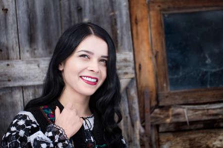 Portret van een aantrekkelijke Roemeense vrouw die omhoog kijkt, met mooi lang golvend donker haar en rode lippen, staande voor een oude houten schuur, gekleed in een traditionele geborduurde volksblouse en vest Stockfoto