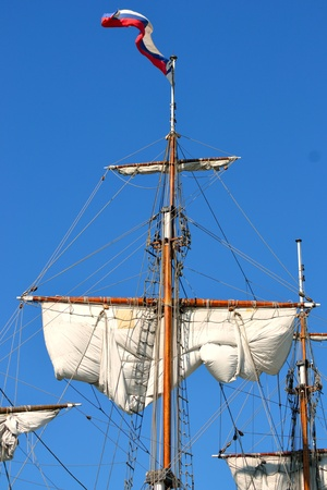 Masts and sails, old sailing ship on the sky background. photo